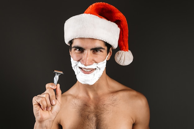 Close up of handsome shirtless man wearing santa claus hat standing isolated, holding a razor, shaving
