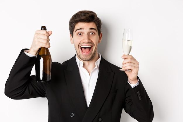 Primo piano di un bell'uomo sorridente in abito nero, che fa un brindisi, tiene in mano champagne e bicchiere, festeggia il nuovo anno, in piedi su sfondo bianco