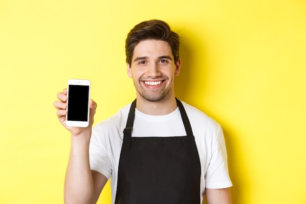 Close-up of handsome waiter in black apron showing smartphone screen, recommending app, standing over yellow background.