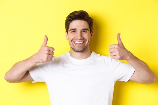 Primo piano del bel giovane che mostra i pollici in su, approva e accetta, sorridendo soddisfatto, in piedi su sfondo giallo.