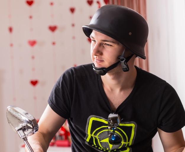 Закройте вверх красивого молодого человека, одетого в черную повседневную рубашку с висячими солнцезащитными очками и велосипедного шлема, смотрящего слева от кадра.