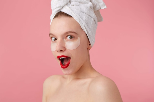 Close up of happy amazed lady after spa with a towel on her head, with patches under the eyes and red lips, with wide open mouth and eyes, hears cool news, stands.