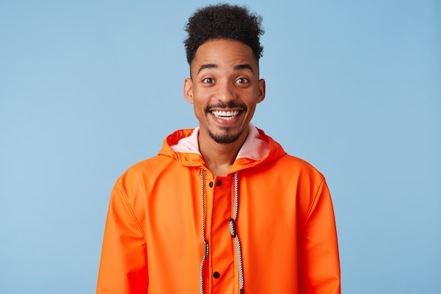 Close up of happy amazed young african american dark skinned man, feels great, wears in orange rain coat, broadly smiles isolated.