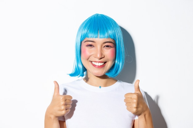 Close-up of happy asian girl in blue wig, smiling and showing thumbs-up in approval