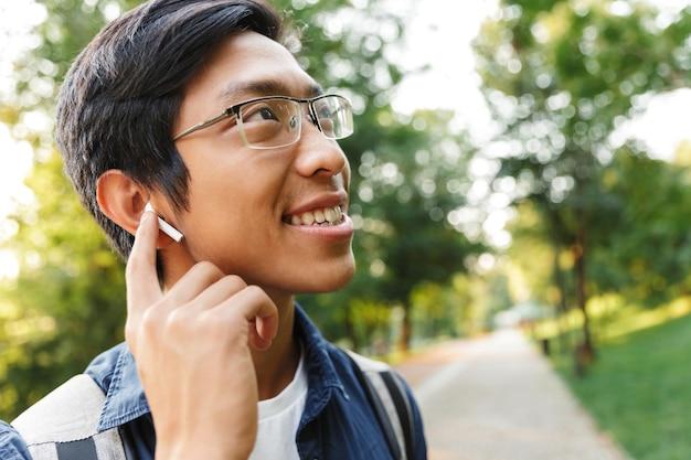 Крупным планом счастливый азиатский студент-мужчина в очках и наушниках, слушающий музыку цршду дщщлштп фцфн