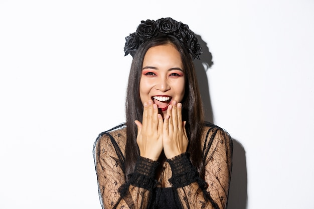 Close-up of happy asian woman celebrating halloween in witch costume and laughing, standing over white background.