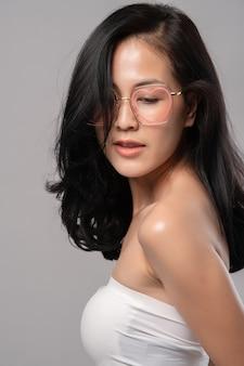 Крупным планом счастливая азиатская женщина носит очки, улыбаясь, глядя в камеру на сером