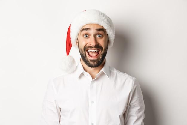 Primo piano del ragazzo barbuto felice in cappello della santa, che sembra sorpreso, festeggia il natale, in piedi