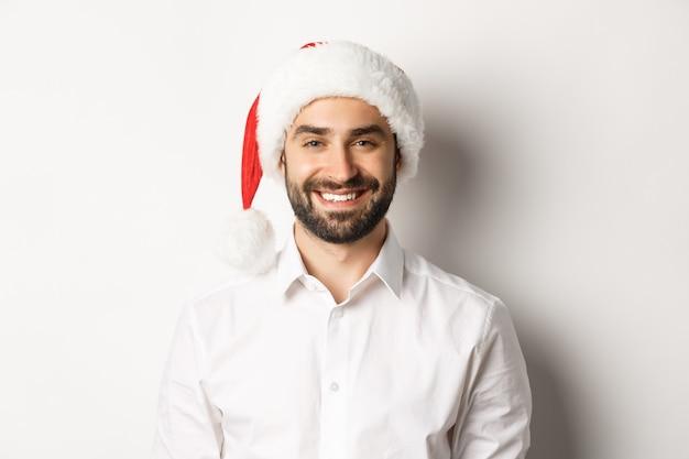 Primo piano di uomo barbuto felice che celebra il natale, indossando il cappello da babbo natale e sorridente, in piedi