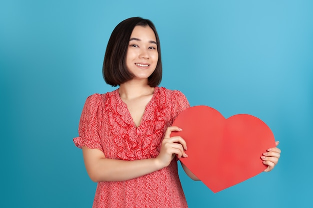 Close-up happy beautiful young asian woman in red dress holding big red paper heart