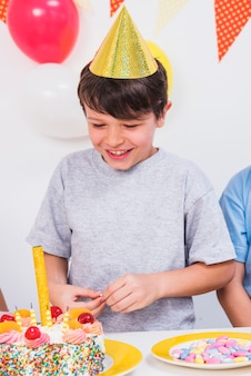 Close-up of a happy boy looking at colorful birthday cake