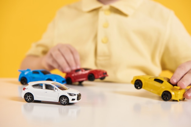 Close up. happy boy plays with model cars.