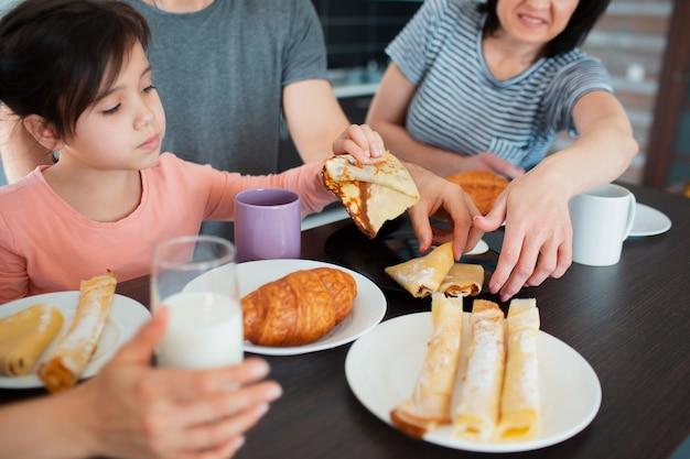 Крупный план. счастливый завтрак большой семьи на кухне. все едят по утрам, болтают и веселятся.