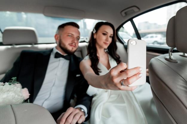 Закройте вверх. счастливые жених и невеста, сидя в шикарной машине.
