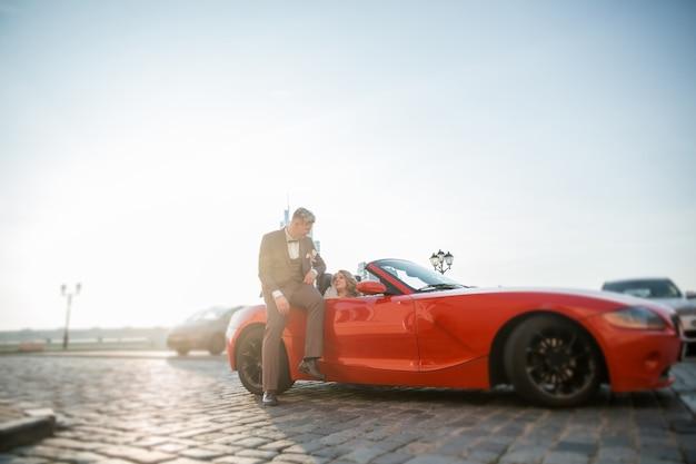 Закройте вверх. счастливые жених и невеста, сидя в роскошном автомобиле.