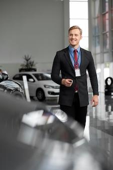 Primo piano su un uomo d'affari felice in una concessionaria di auto