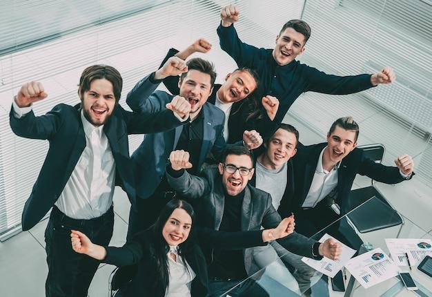 閉じる。オフィスの職場で幸せなビジネスチーム。