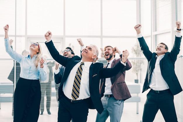Закройте вверх. счастливая бизнес-команда, ликуя в офисе. концепция успеха