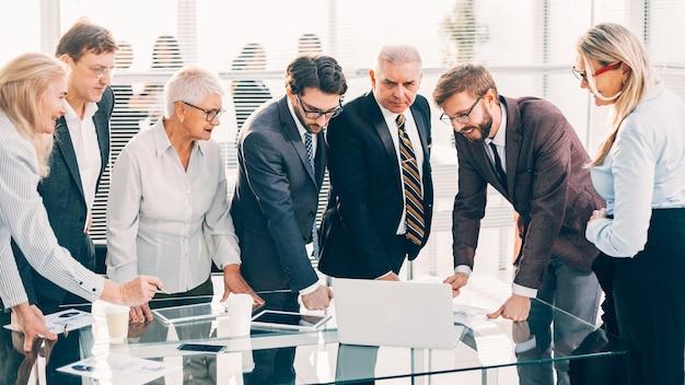 Закройте вверх. счастливая бизнес-команда смотрит на экран ноутбука