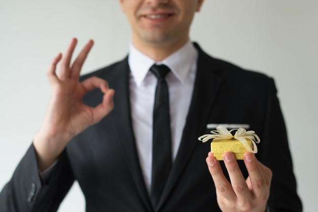 Close-up of happy businessman holding small gift box