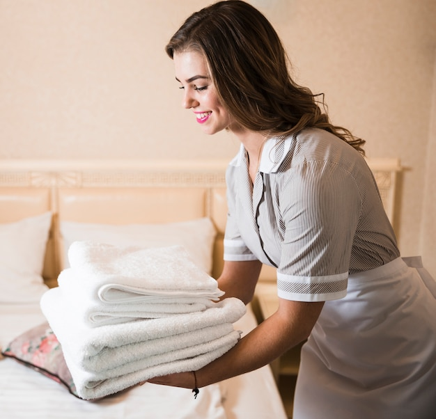 Close-up of happy chambermaid putting stack of fresh white bath towels on the bed