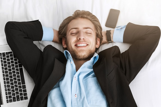 Close up of happy cheerful bearded man in black suit lying on back with laptop computer and cellphone near him with relaxed expression after completing all tasks.