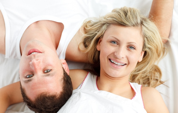 Close-up of happy couple resting in bed