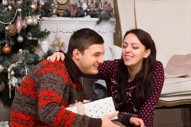 トレンディな長袖の冬のシャツを着て、美しいクリスマスツリーの近くで一緒に笑って、幸せなカップルをクローズアップ