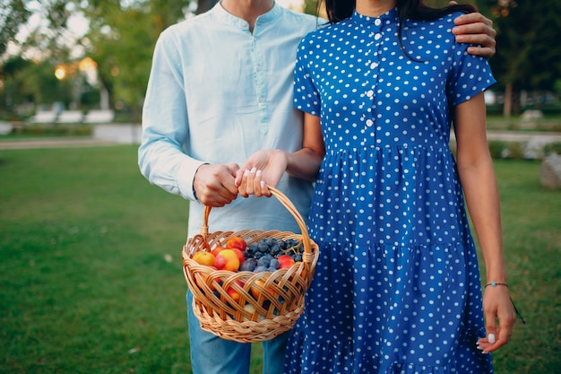 Close up of happy couple with fruits in picnic basket staying in the park.