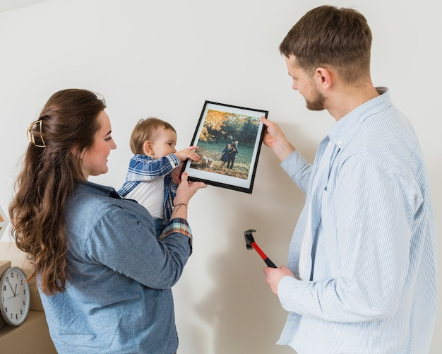 Close-up of happy couple with their baby toddler fixing picture frame on wall