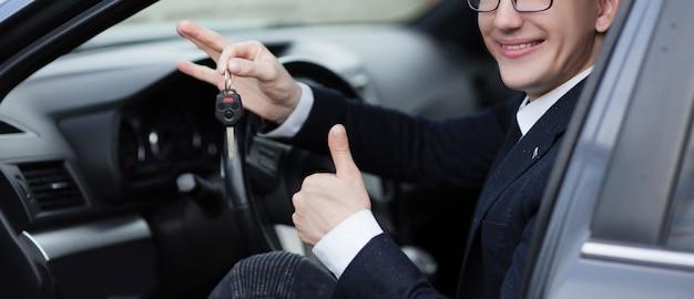 Закройте вверх. счастливый водитель показывает палец вверх, сидя в своей машине