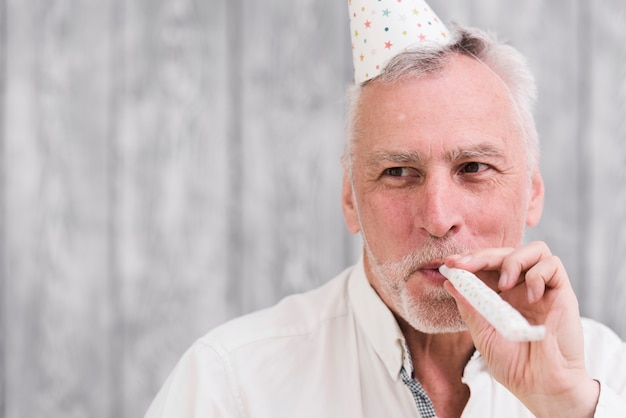Close-up of a happy elder man blowing party blower