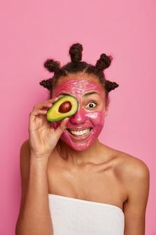 Primo piano sulla donna etnica felice gode di applicare la maschera per il viso isolata