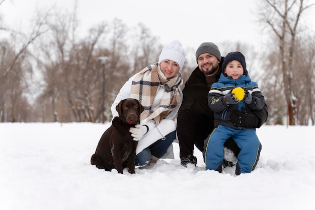 Primo piano sulla famiglia felice che gioca nella neve con il cane