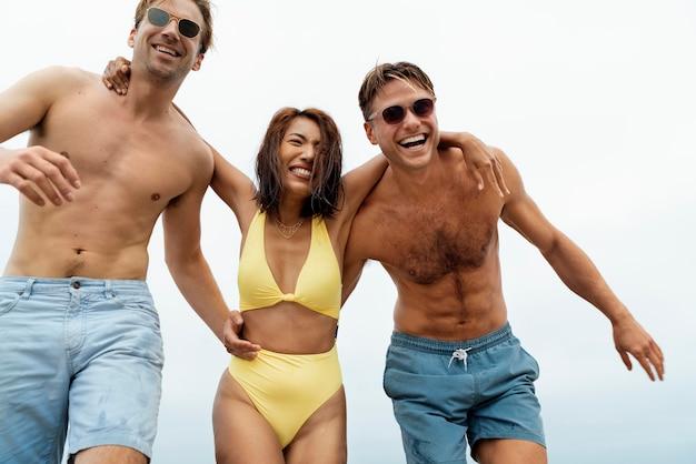 海辺で幸せな友達をクローズアップ