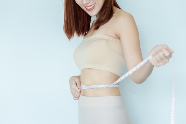 Close up of happy girl measuring her waistline . perfect slim body
