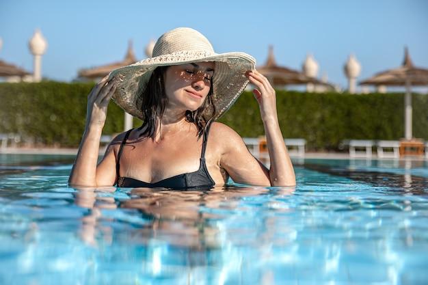 Primo piano di una ragazza felice in un cappello di paglia bagna in piscina con tempo soleggiato. concetto di vacanza e resort.