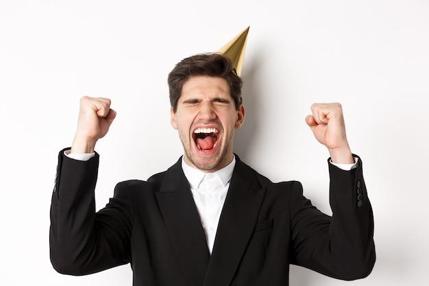 Primo piano di un bell'uomo felice, che indossa cappello e abito da festa, alzando le mani e gioendo, festeggiando il nuovo anno, in piedi su sfondo bianco.