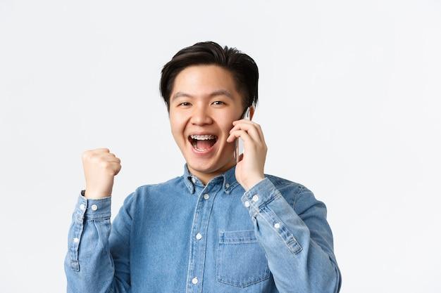Primo piano di un bel ragazzo asiatico felice che si rallegra di grandi notizie, parla al telefono cellulare e pompa a pugno, trionfa e dice di sì, raggiunge l'obiettivo. l'uomo riceve una chiamata dal datore di lavoro, ha un lavoro, sfondo bianco