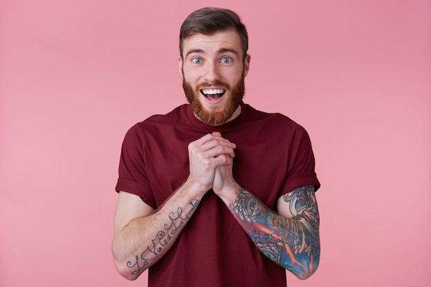 Close up of happy handsome bearded young man with tattooed hand, saw something cute and smiling, looking at camera isolated over pink background.