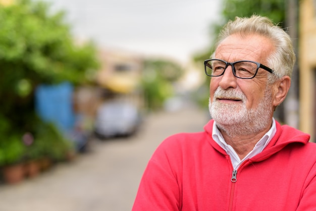 Close up of happy handsome senior bearded man smiling while thinking and looking up with eyeglasses outdoors