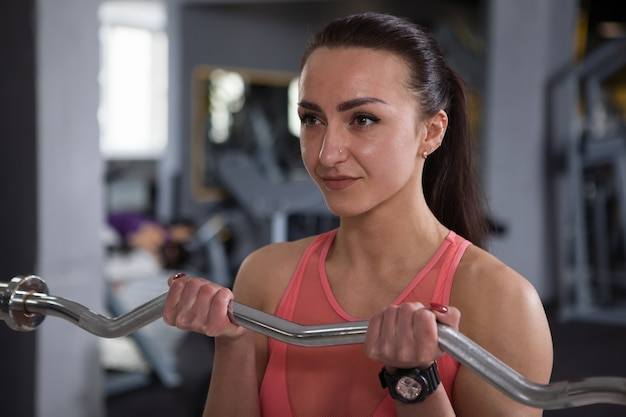 Close up of a happy healthy strong sportswoman doing biceps curls with barbell