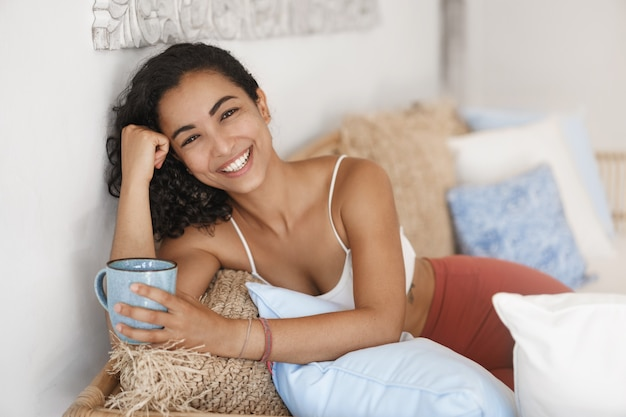 Close-up happy healthy young woman with dark curly hair lying in comfortable sofa in a terrace