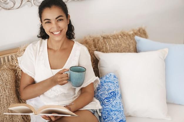 テラスの快適なソファに横たわっている暗い巻き毛のクローズアップ幸せな健康な若い女性