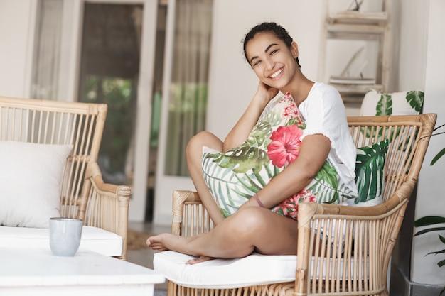 테라스에서 편안한 소파에 앉아 검은 곱슬 머리를 가진 근접 행복 건강한 젊은 여자
