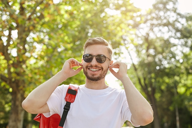 Close-up of happy hipster walking through park on sunny day, wearing sunglasses and white t-shirt, inserting headphones into ears, being in nice mood