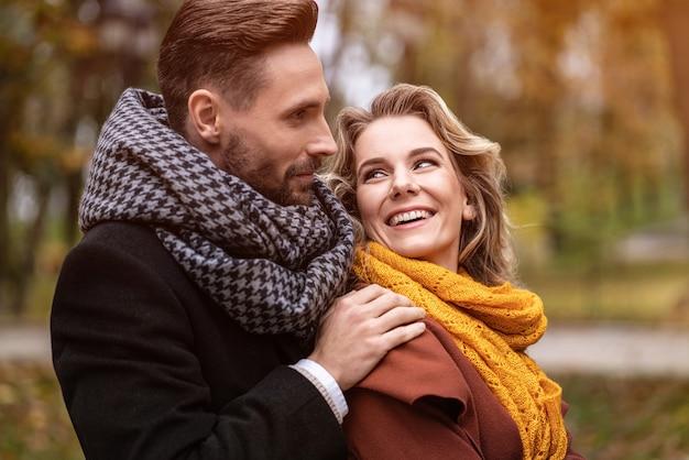 Закройте вверх. счастливые в любви молодые люди, мужчина обнимает женщину сзади, когда она смотрит на него, счастливая