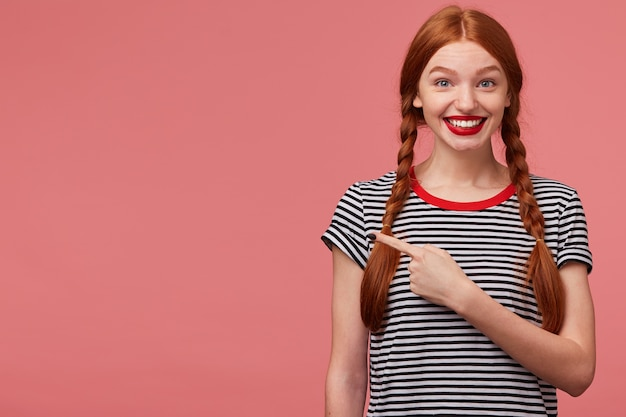 Close up of happy inspired red haired teen girl shows with index finger on the empty space on left side,is delighted with the product, advises to pay attention,place for your advertisement