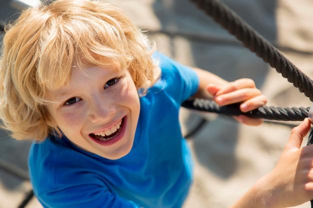 Крупным планом счастливый ребенок скалолазание