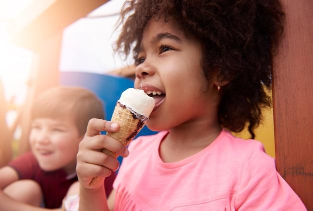 Chiuda in su bambino felice che mangia il gelato